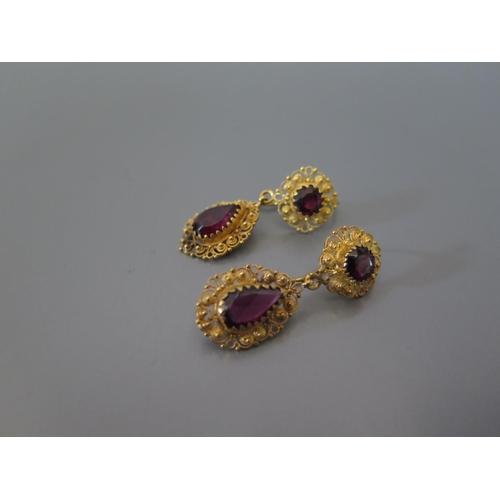 195 - A Pair of Garnet Pendant Earrings in a precious yellow metal filigree mount, 8.1g...