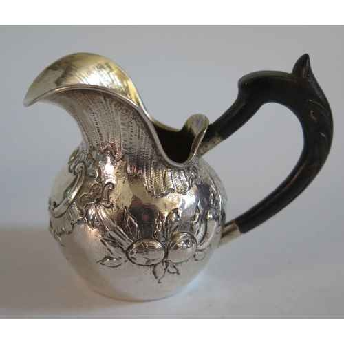 57 - .800 Continental Silver Creamer with repousse scroll and fruit decoration, 70g gross...