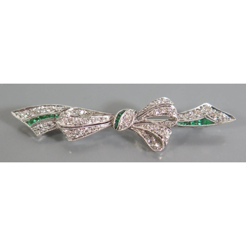 184 - An Emerald and Diamond Ribbon Brooch in a precious white metal setting, c. 56mm, 6.1g ETD 1ct...