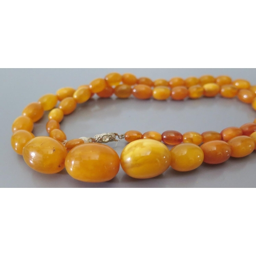 215a - A Butterscotch Amber Bead Necklace 42.9g (largest bead c. 22 x 16mm) AND bracelet 7.5g...
