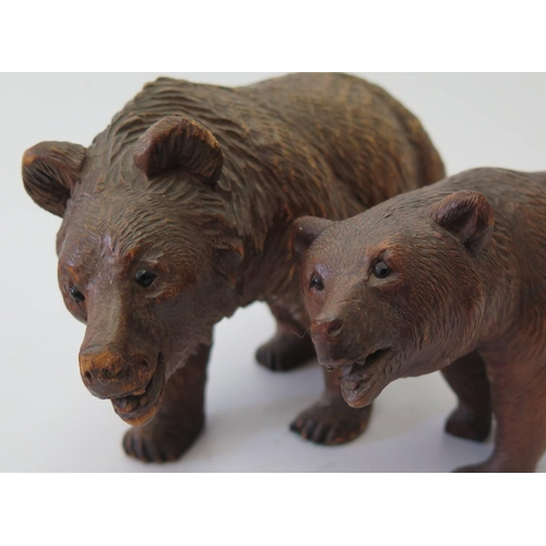 303b - A Pair of Graduated Black Forest Carved Wooden Bears, largest 21cm long...
