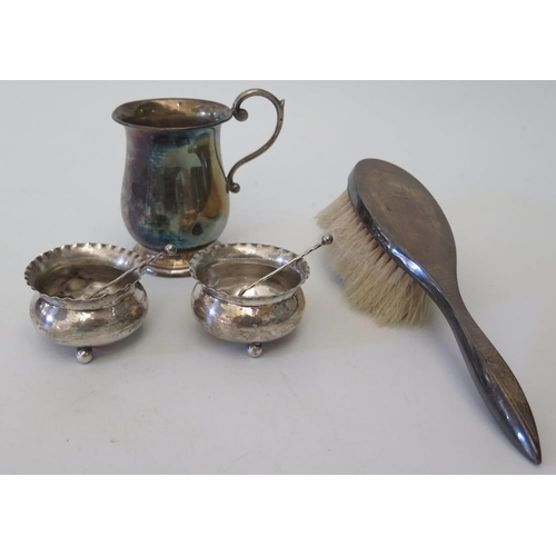 37 - A silver christening mug, pair of silver salts with spoons and silver backed hair brush...