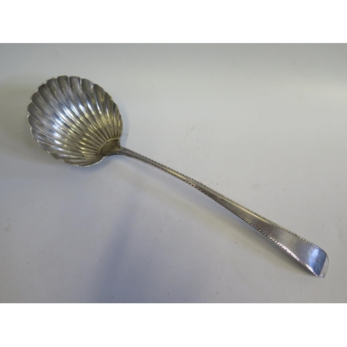 16 - An Early 19th Century Bright Cut Silver Soup Ladle with scalloped bowl, possibly provincial, maker's...