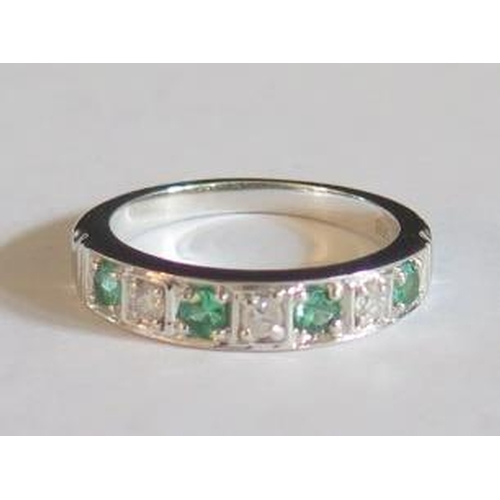 25 - A 9K White Gold, Emerald and Diamond (.15ct) Seven Stone Ring, size M.5...