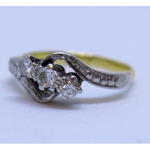 13 - A Diamond Three Stone Cross Over Ring (rubbed UK marks), size H, 2.5g...