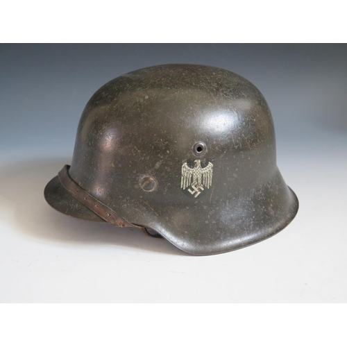 396 - A WWII German Army SD Helmet, rim stamped 1753, with leather chin strap...