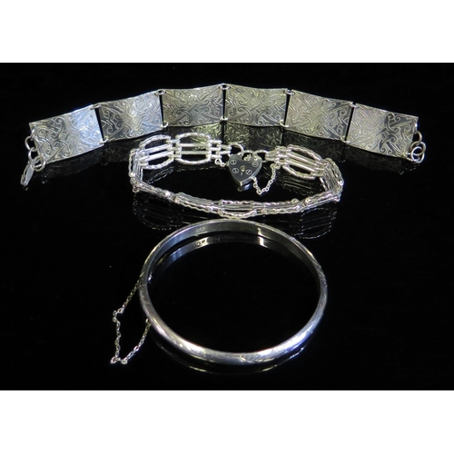 1 - A Hinged Silver bangle with chased decoration, gate link silver bracelet and one other silver bracel...