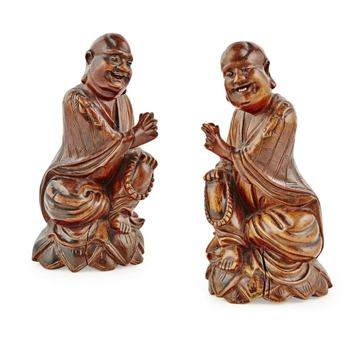 10 - PAIR OF WOODEN FIGURES OF LUOHAN<br><br>LATE QING DYNASTY <br><br>supported on a lotus plinth, each ...