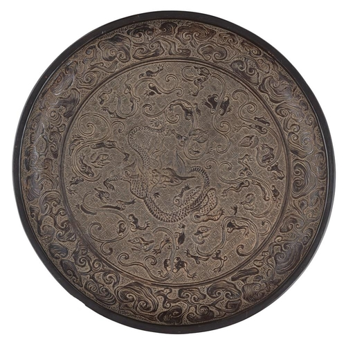 13 - BLACK LACQUER 'NINE DRAGONS' DISH<br><br>POSSIBLY YUAN DYNASTY <br><br>crisply carved in shallow rel...