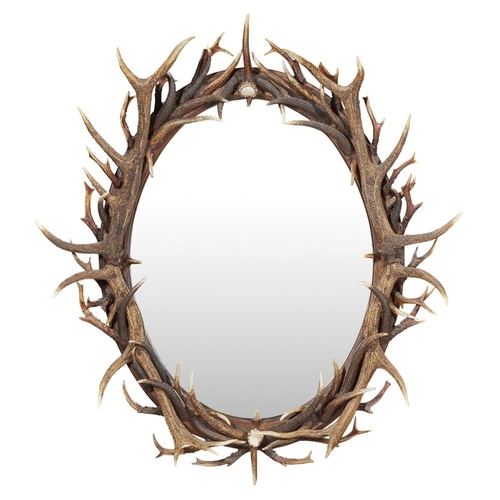 28 - AN ANTLER FRAMED OVAL MIRROR<br><br>CONTEMPORARY <br><br>the oval mirrored plate enclosed by entwine...