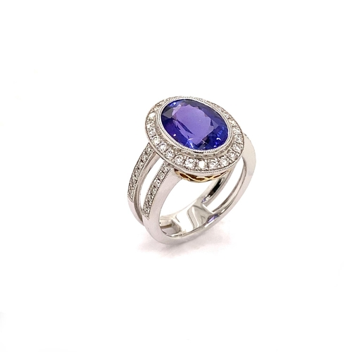 15 - A DOUBLE SHANK HALO DESIGN TANZANITE AND DIAMOND RING <br /><br />Crafted in 18K White Gold, the Dou...