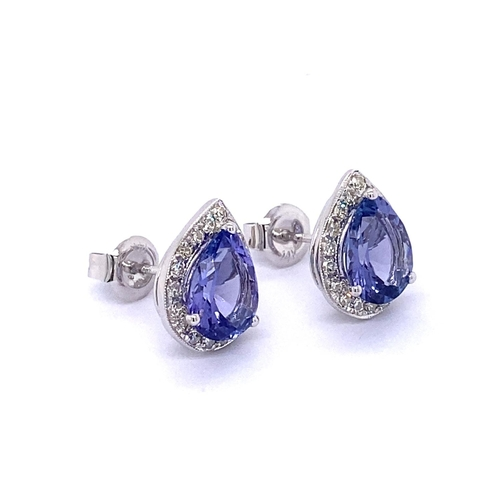 29 - A PAIR OF HALO DESIGN TANZANITE AND DIAMOND STUD EARRINGS <br /><br />Crafted in 14K White Gold, the...