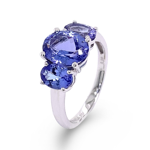 31 - A TRILOGY OVAL CUT TANZANITE RING <br /><br />A Trilogy Tanzanite Ring crafted in 18K White Gold, se...
