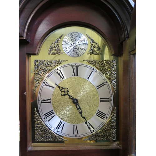 50 - A mahogany longcase clock, the arched hood over a brass dial and glazed trunk door, the German movem...