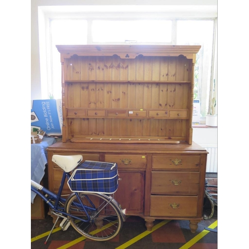 10 - A pine dresser with associated rack, the rack with trinket drawers, 137 cm wide, over a dresser with...