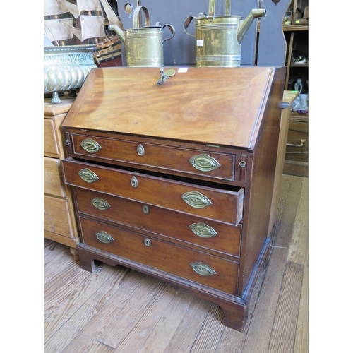 22 - An early 19th century mahogany bureau, the sloping fall enclosing pigeon-holes and drawers, over fou...