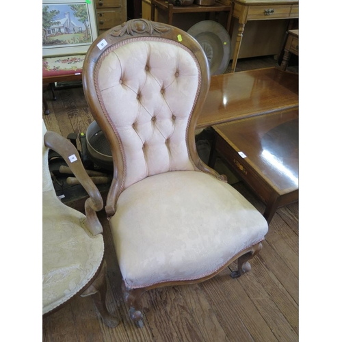 25 - A Victorian walnut nursing chair, the cabochon carved button back on moulded cabriole legs and pot c...