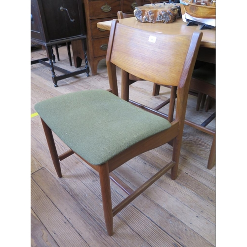29 - A set of six 1970s teak dining chairs, with broad top rails and padded seats, on turned legs, and a ...
