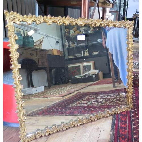 3 - A foliate scroll gesso framed wall mirror, with rectangular plate, 68 x 57 cm...