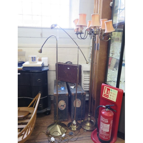 33 - A brass six light standard lamp, the scroll arms on a reeded column, with circular base and paw feet...