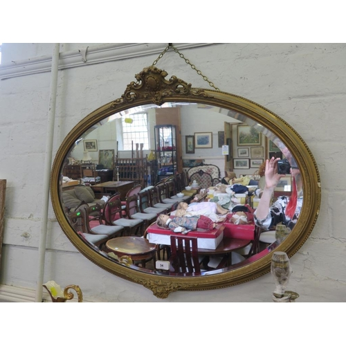 34 - A giltwood oval wall mirror, the beaded frame with cabochon and foliate mounts, enclosing a bevelled...