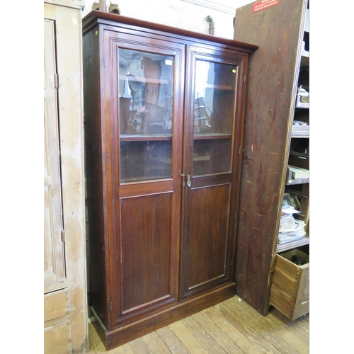 4 - A mahogany bookcase, with twin glazed and panelled doors, 101 cm wide, 30 cm deep, 168 cm high...