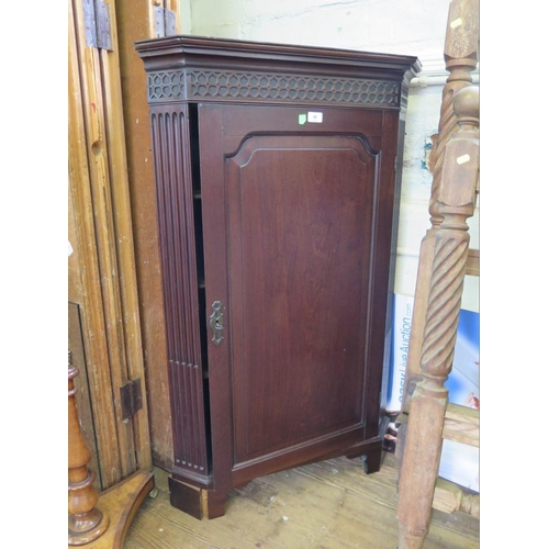 40 - A George III style mahogany corner cabinet, the blind fret carved frieze over a panelled door and st...