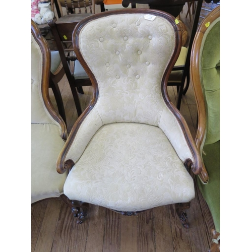 7 - A Victorian walnut nursing chair with cream button upholstery, on cabriole legs and pot castors...