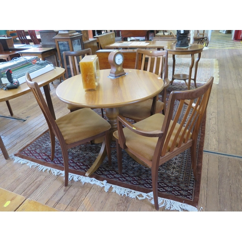 18 - A set of four G-Plan dining chairs, including two carvers, with rail backs, and a circular teak supp...