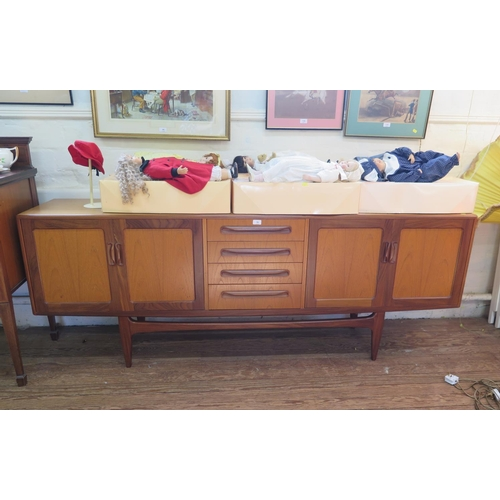 19 - A G-Plan teak sideboard, the four central garduated drawers flanked by twin cupboard doors, on taper...