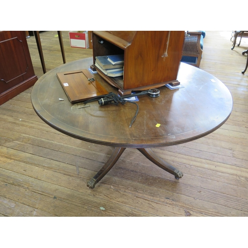 21 - A crossbanded mahogany circular coffee table, on four outsplayed legs with brass lion paw feet and c...