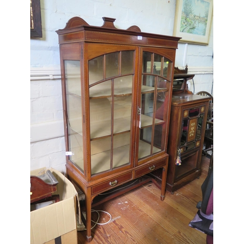44 - An Edwardian boxwood and ebony strung mahogany display cabinet, the shaped back over a pair of glaze...
