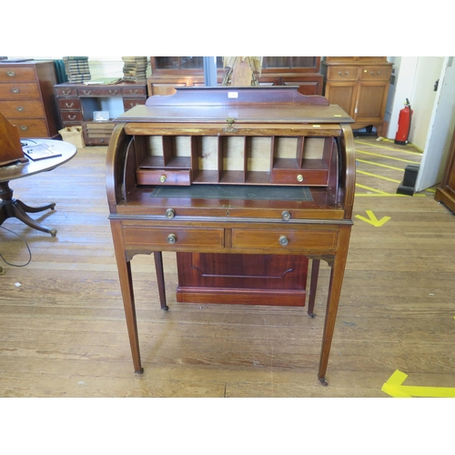 6 - An Edwardian inlaid mahogany roll top desk, the scroll and urn inlaid top enclosing pigeon-holes and...