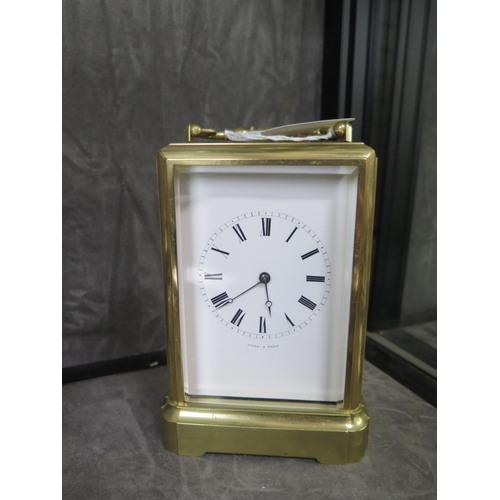 61 - A brass carriage clock, inscribed Jules a Paris, with bevelled glass panels and inscribed enamel dia...