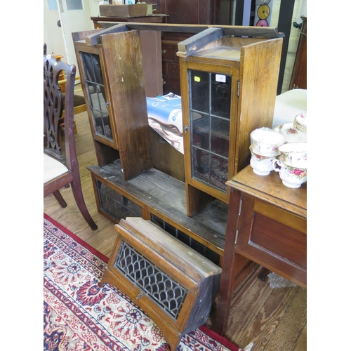 11 - An oak and lead glazed desk top bookcase, the two glazed flaps over a centre flap flanked by a pair ...