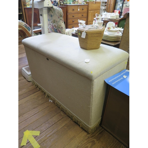 2 - A large upholstered ottoman box, with hinged lid and later castors, 125 cm wide, 56 cm deep, 77 cm h...
