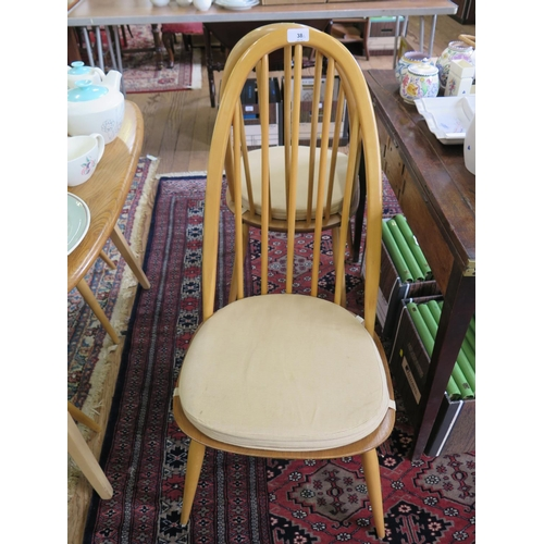 38 - An Ercol elm and beech Windsor dining suite, comprising an extending dining table, with two extra le...