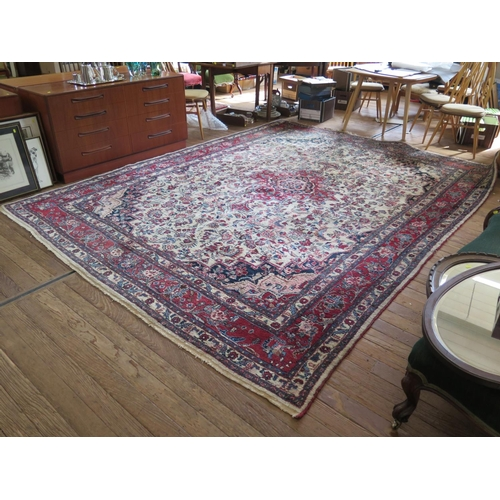 57 - A Sarouk design carpet, the central red medallion in an ivory field filled with foliate designs in a...