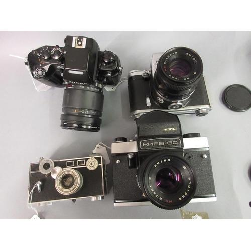 112 - Pentacon Six TL SLR camera, a Nikon F4 SLR camera and a similar Russian camera together with a mid 2...