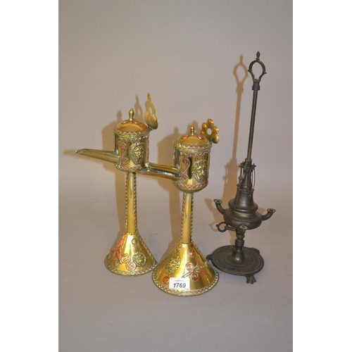 1769 - Pair of oriental brass and copper mounted oil lamps together with another Middle Eastern bronzed met...