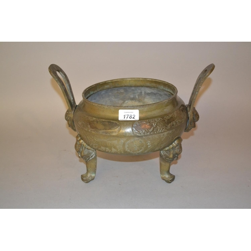 1782 - Oriental patinated bronze two handled incense burner, raised on mask head supports...