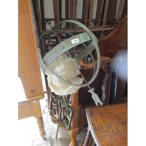 1909 - Patinated metal and wrought iron armillary sphere on a scroll work base, (arrow head missing), 15ins...