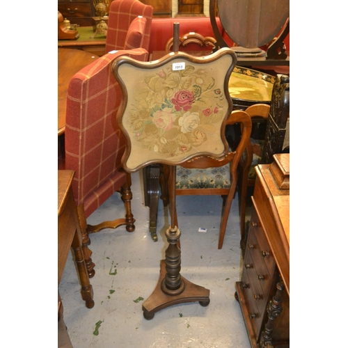 1913 - 19th Century mahogany and rosewood pole screen, the shaped adjustable needlepoint panel above a turn...