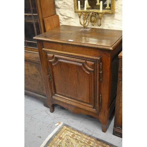 2400 - 18th Century French oak side cabinet, the moulded plank top above a single shaped carved and fielded...
