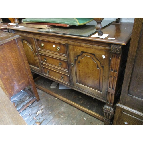 2410 - Reproduction oak sideboard with three centre drawers flanked by panel doors on square carved taperin...