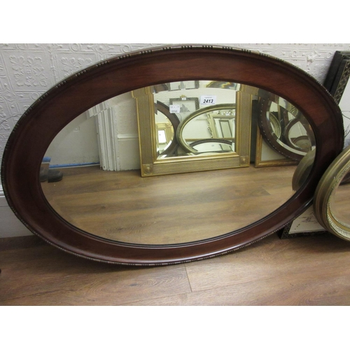 2413 - 1920's Oval mahogany bevel edged wall mirror together with a reproduction oval gilt framed bevel edg...