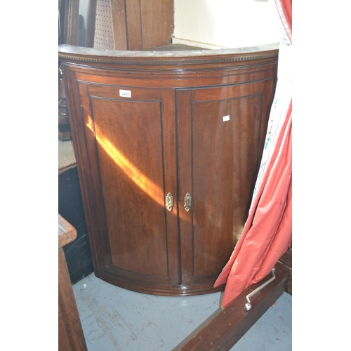 2449 - George III mahogany two door bow front hanging corner cabinet with a moulded dentil cornice...