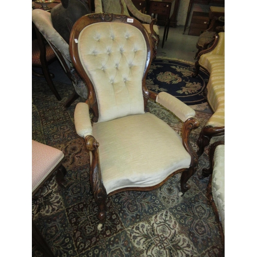2453 - Victorian carved walnut and button upholstered open arm drawing room chair upholstered in a beige fa...