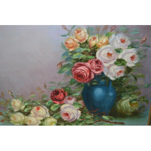 1180 - L. Durante, 20th Century oil on canvas, still life study of roses in a blue vase, dated 1945, unfram...