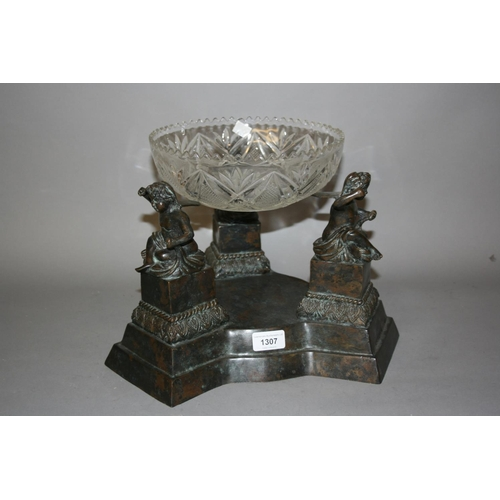 1307 - 20th Century bronze patinated stand mounted with figures of seated cherubs, with associated glass fr...